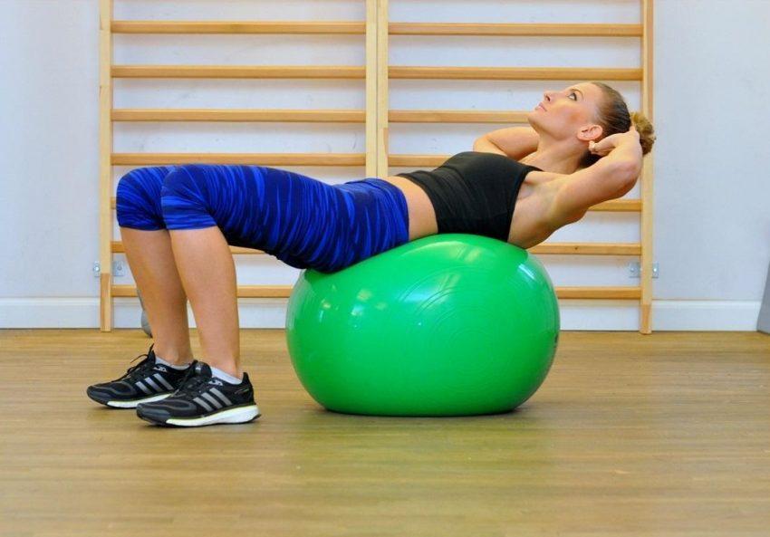 Trenerka pokazuje, jak ćwiczyć na piłce fitness. Leży na plecach na piłce, ręce trzyma pod głową