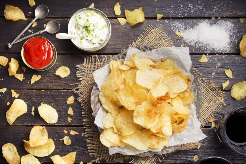 Chipsy ziemniaczane z dipem na drewnianym stole.