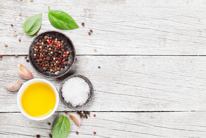 Widok na biały, drewniany blat. Na nim trzy miski z oliwą, pieprzem i solą. Dookoła rozsypany pieprz i liście