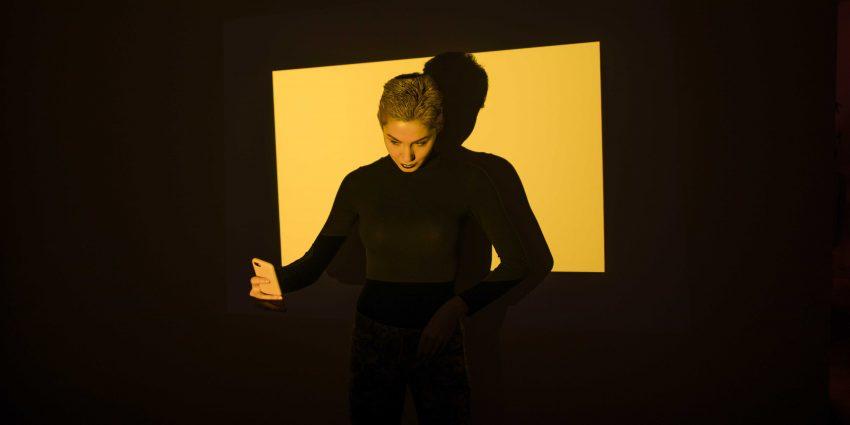 kobieta robiąca selfie, oświetlona na żółto
