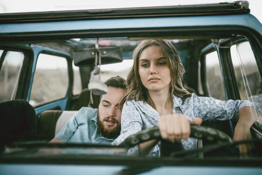 Kobieta prowadzi auto. Obok siedzi mężczyzna, który śpi, opierając sie o ramię kobiety