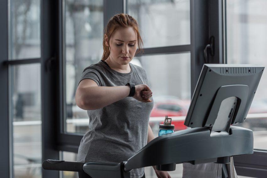 Kobieta ćwiczy na bieżni, na siłowni, patrząc na zegarek. Za nią jest duże okno.