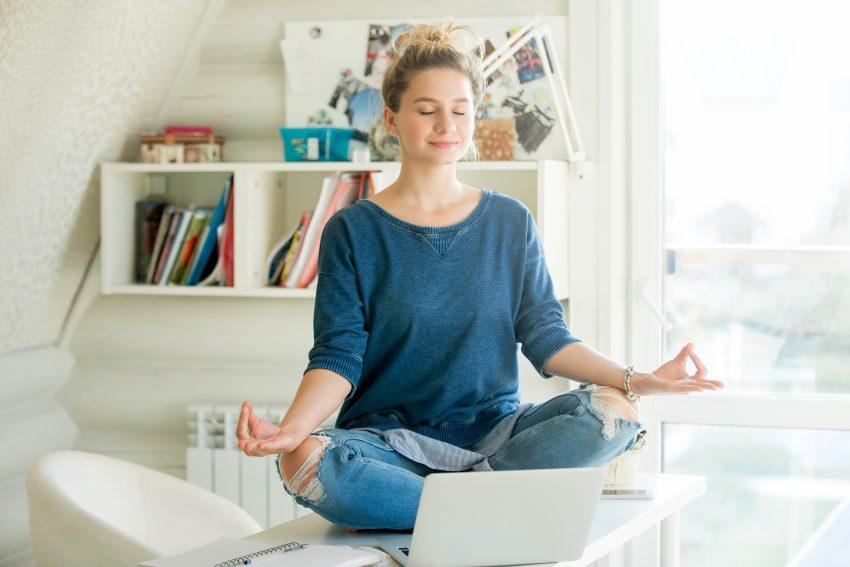 Kobieta siedzi po turecku na biurku i medytuje. Przed nią stoi na biurku laptop, za nią regał z książkami, fotel i okno