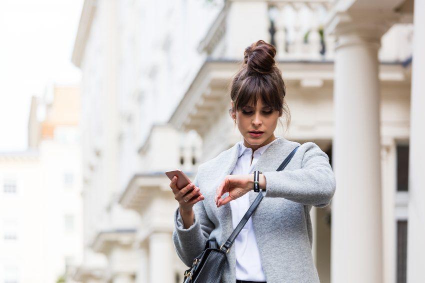 Kobieta uczesana w koka, w jasnym płaszczu i koszulce patrzy na zegarek, trzymając telefon. Widać, że brakuje jej czasu i jest spóźniona