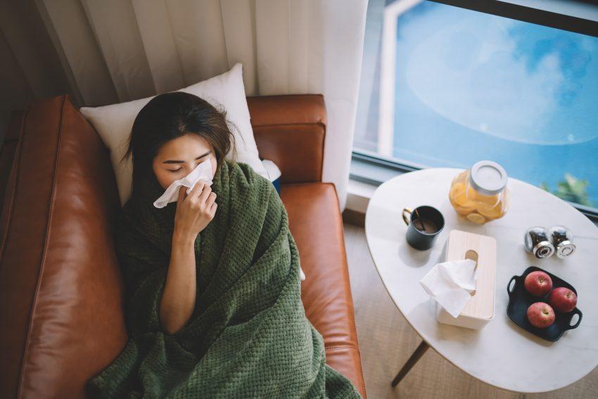 Kobieta leży na skórzanej kanapie, pod kocem, podparta na poduszce i wyciera nos chusteczką. Obok na owalnym stoliku stoją jabłka, słoik pudełko z chusteczkami i kubek z cherbatą.