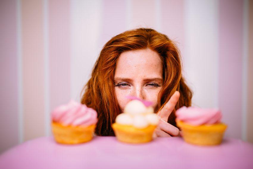 Kobieta zerka na trzy babeczki i zastanawia się, którą zjeść