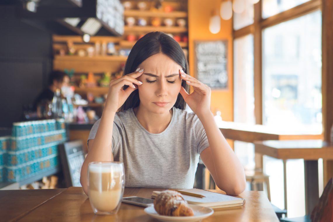 Dziewczyna z czarnymi włosami siedzi w kawiarni z kawą i rogalikiem, podpiera głowę, ponieważ ją boli, ma zamknięte oczy i zmarszczone czoło.