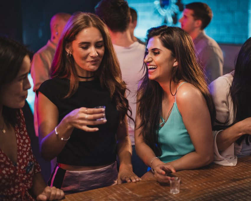 Trzy kobiety stoją przy barze w klubie, jeda pije drinka. Śmieją sie i rozmawiają