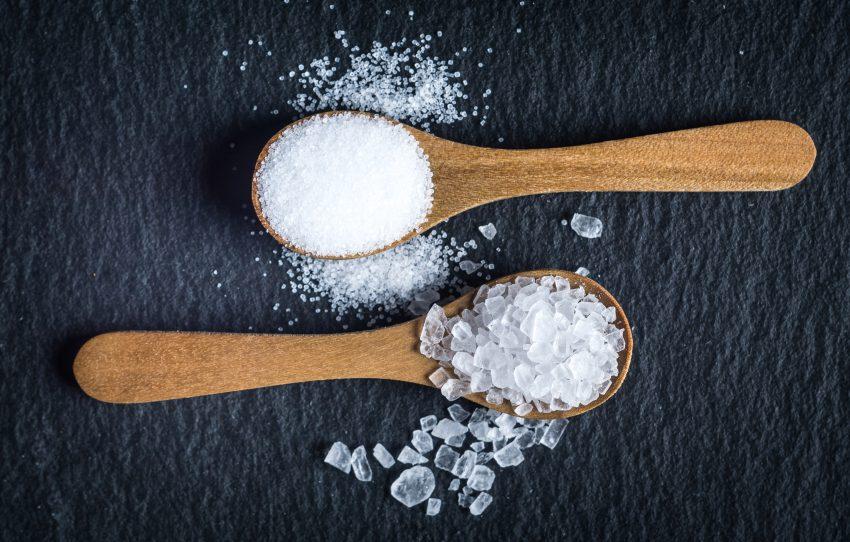 WIdok na dwie drewniane łyżeczki, w których jest sól. Dwa rodzaje soli - kuchenna i morska. Wszytsko na ciemnym tle.