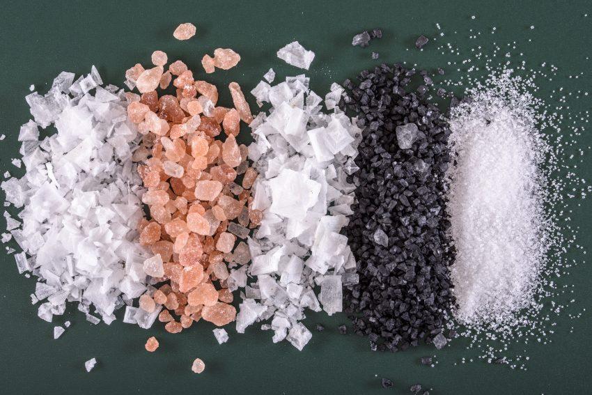 5 rodzajów soli rozsypanych na czarnym tle i ułożonych w grube paski obok siebie.