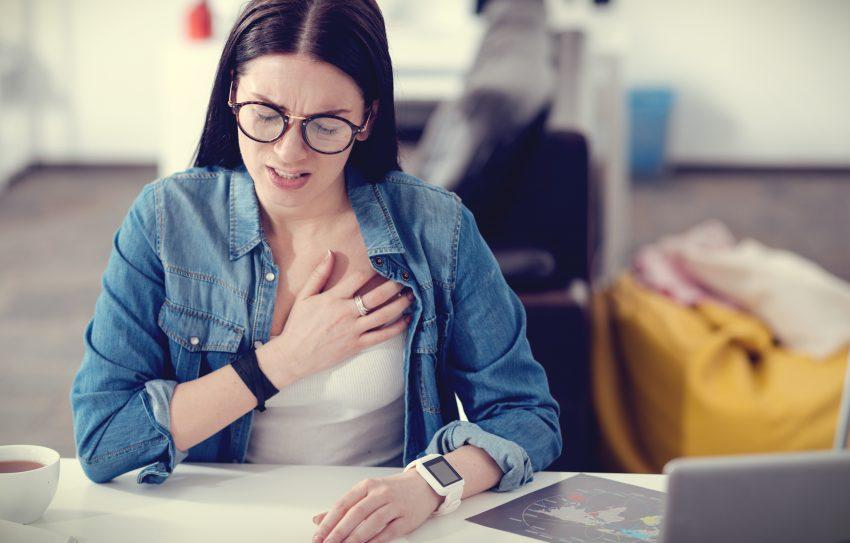 Młoda dziewczyna siedzi za biurkiem. Ma okulary, trzyma się za klatkę piersiową. Prawdopodobnie boli ją serce