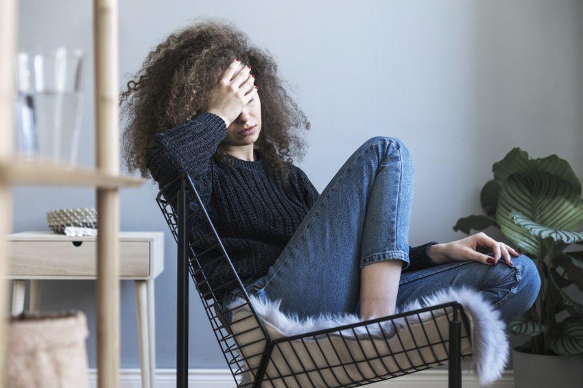Kobieta siedzi w fotelu i trzyma się za głowę. Boli ją głowa. Ma kręcone włosy