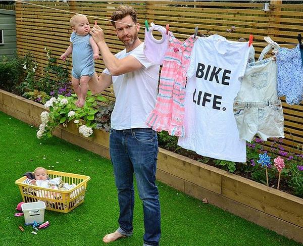 Ojciec w ogródku wiesza pranie i przypina też dziecko klamerkami do sznurka. Na dole lezy drugie dziecko w małej kołysce.
