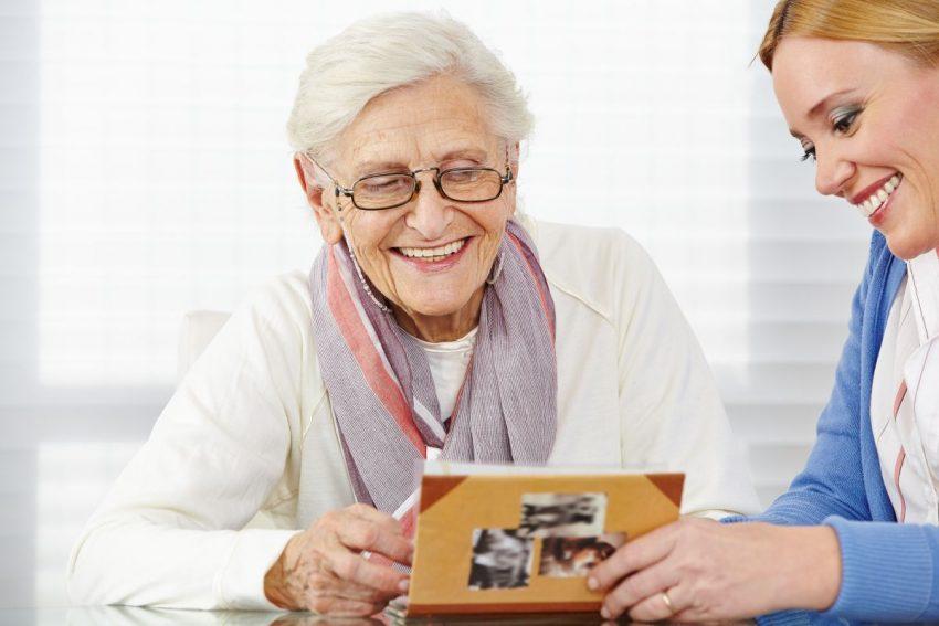 Starsza i młodsza kobieta z uśmiechem oglądają zdjęcia w albumie