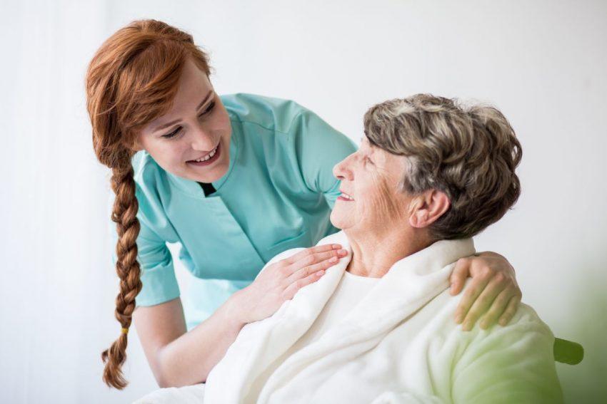 Pielęgniarka pochyla się nad chorą na Alzheimera kobietą