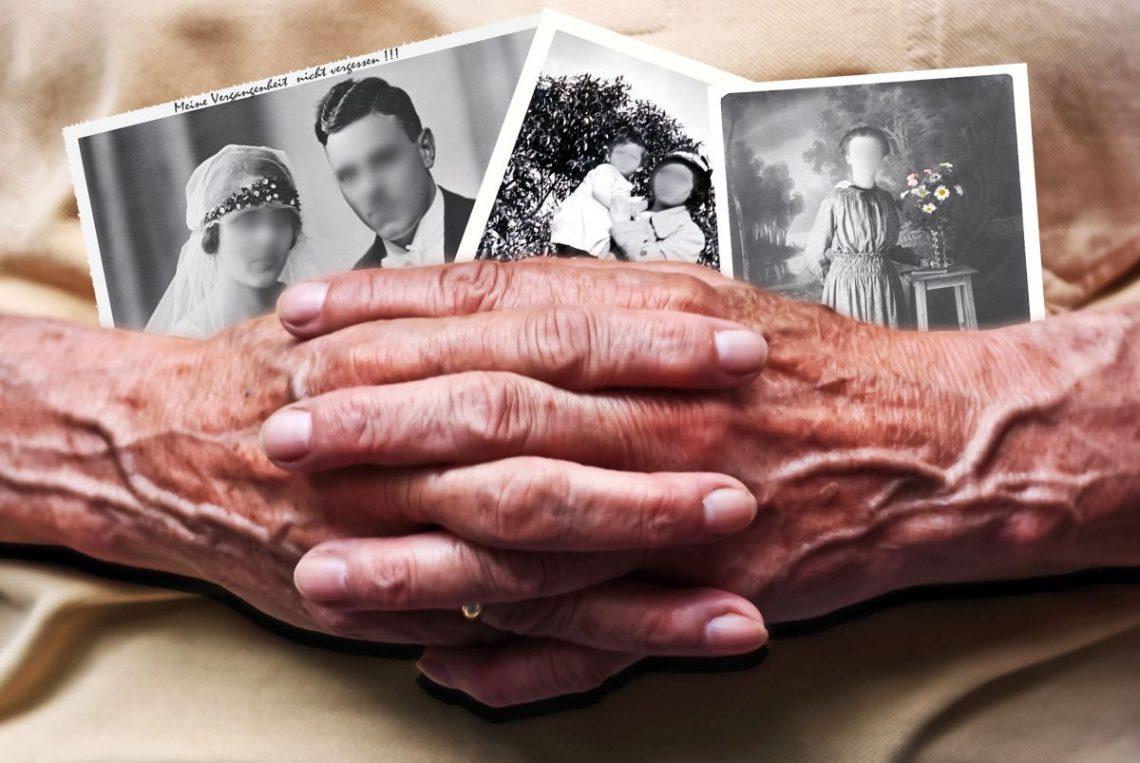 Dłonie starszej kobiety z czarno-białymi zdjęciami