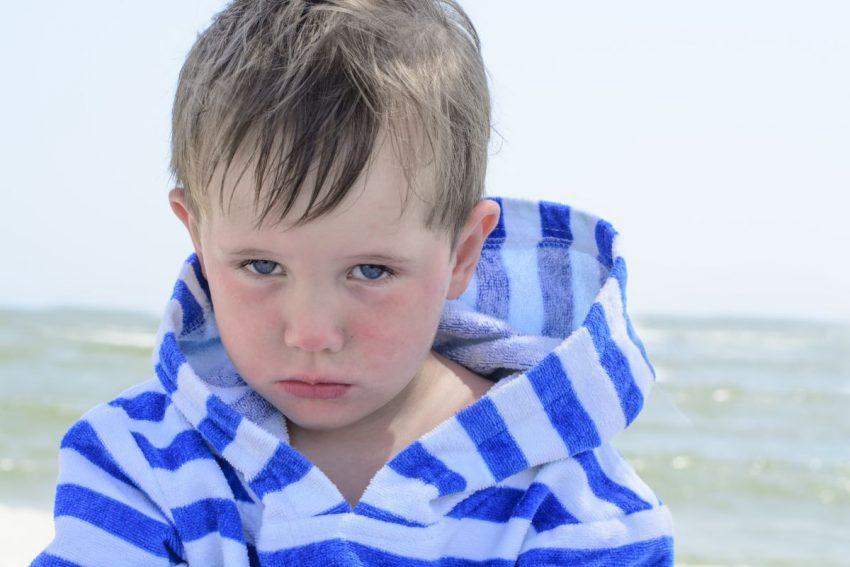 Smutny chłopiec z atopowym zapaleniem skóry