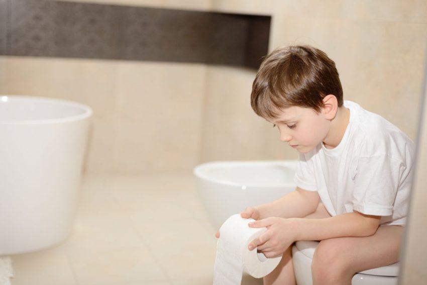Mały chłopiec siedzi na toalecie z powodu biegunki
