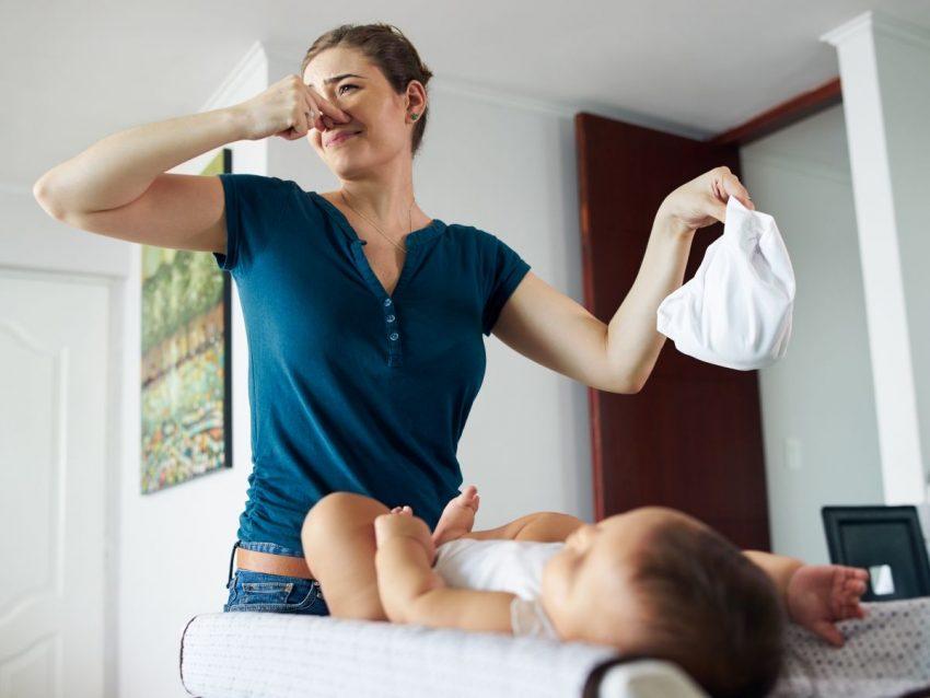 Kobieta trzyma śmierdzącą pieluszkę swojego dziecka
