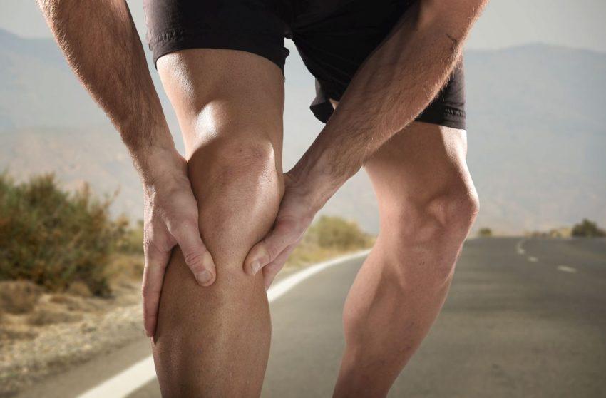 Mężczyzna trzyma się za wewnętrzną stroną kolana