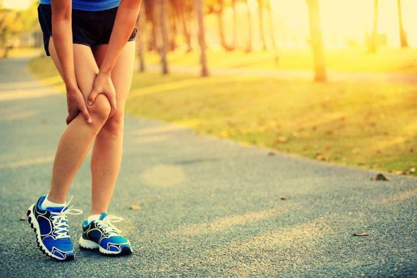 Biegacz trzyma się za bolące z tyłu kolano
