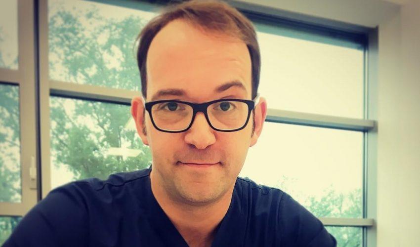 chirurg Paweł Kabata sodchyla sięod biurka na którym stoi komputer