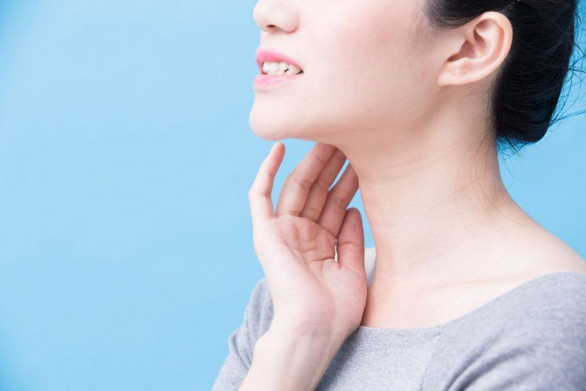 Zdjęcie kobiety z profilu, trzymającej się jedną ręką za szyję