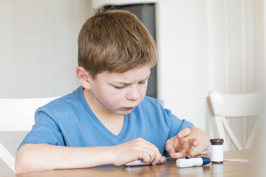 Chłopiec chory na cukrzycę typu 1 sprawdza poziom cukru we krwi