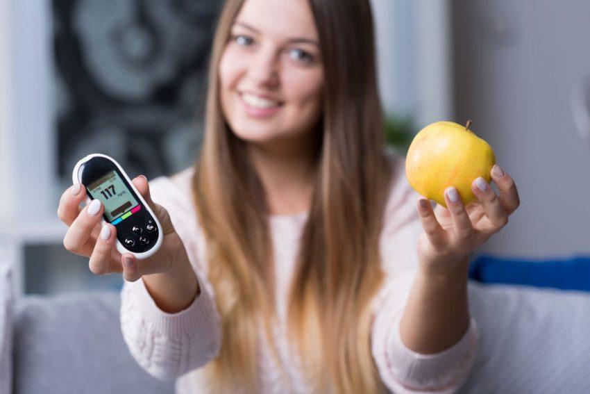 Kobieta chora na cukrzycę typu 2 trzyma jabłko i glukometr