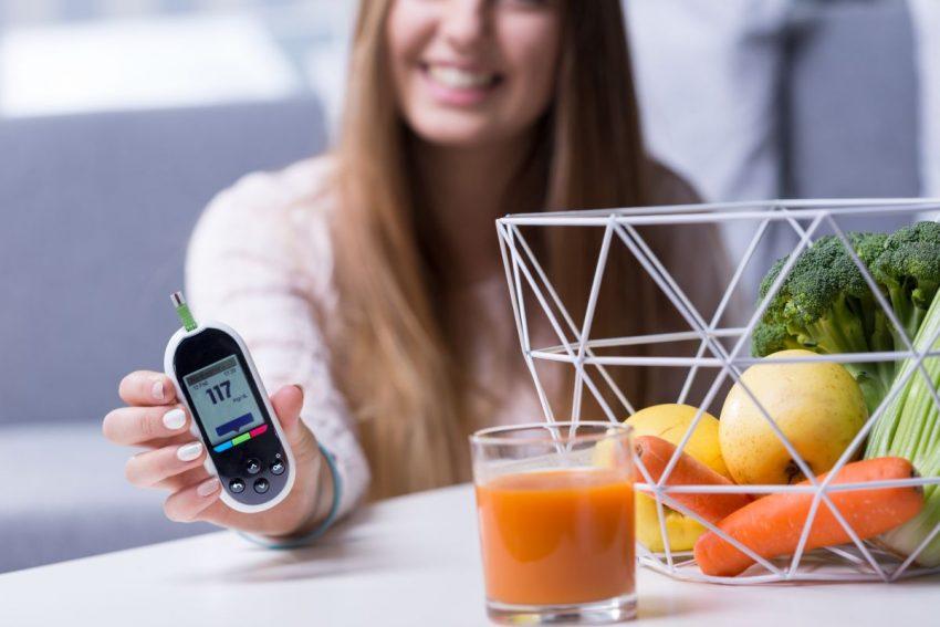 Kobieta z glukometrem i sokiem z jadłospisu dla cukrzyka typu 2