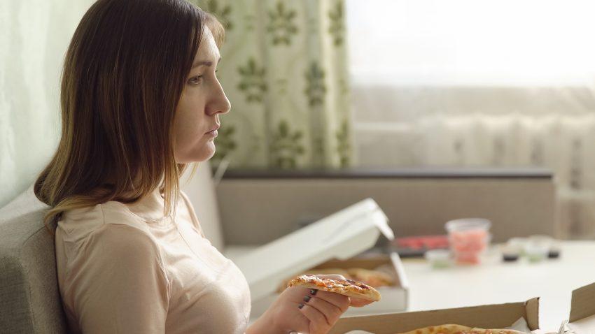 Smutna kobieta siedzi na kanapie z pizza i ogląda telewizję.