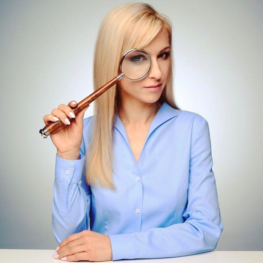 młoda kobieta w niebieskiej koszuli z ogromną lupą przy oku