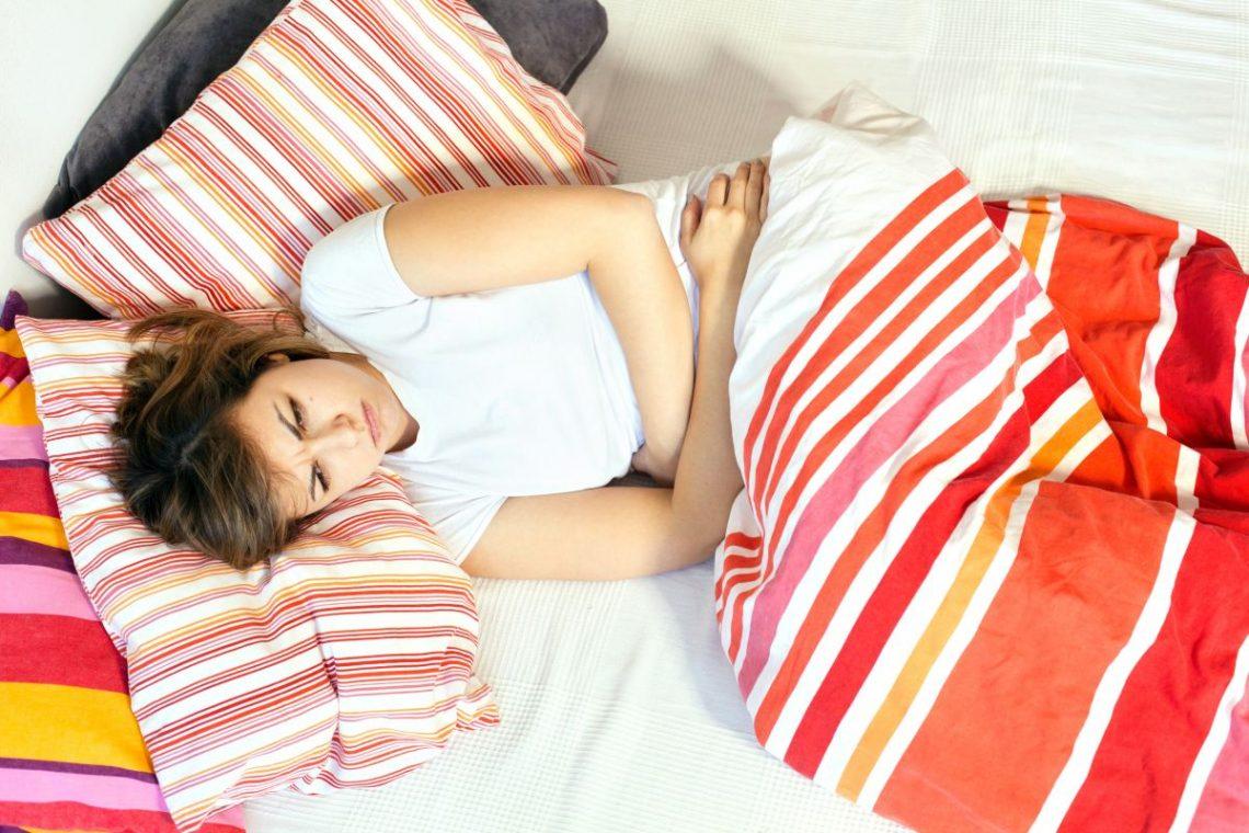 Kobieta w łóżku chora na grypę żołądkową