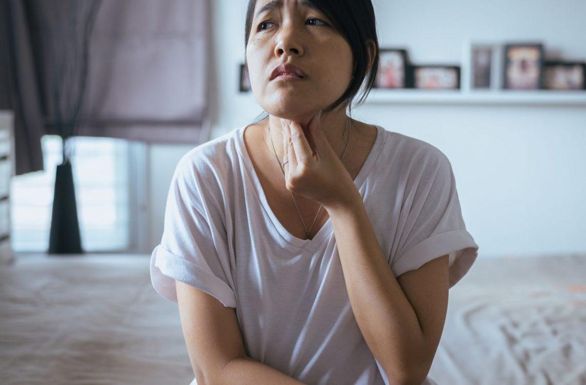 Kobieta w ciąży z chorobą hashimoto trzyma się za gardło
