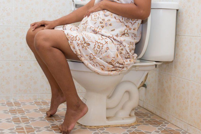 Kobieta w ciąży siedzi w łazience z powodu hemoroidów