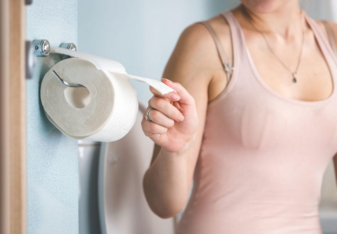Kobieta urywa papier toaletowy z powodu hemoroidów zewnętrznych
