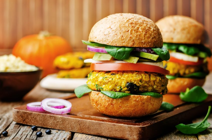 vegan millet black bean pumpkin burgers on a dark wood backgroundthe toning. selective focus.