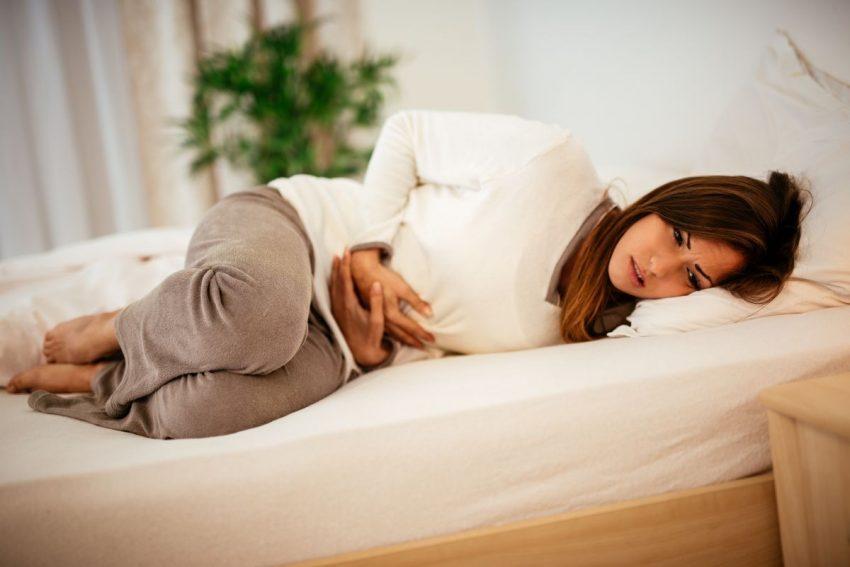 Kobieta leży i trzyma się za brzuch z powodu kłucia w brzuchu