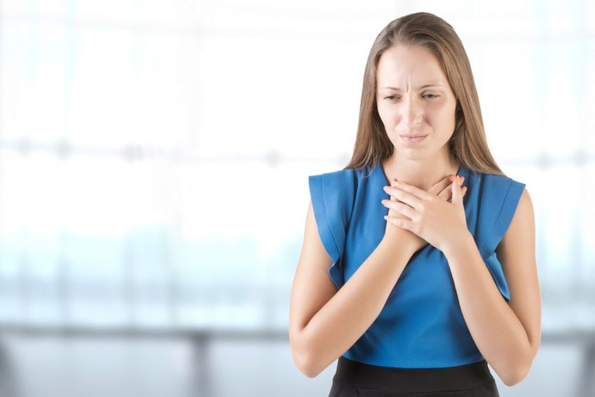 Kobieta z objawami mononukleozy trzyma dłonie na klatce piersiowej