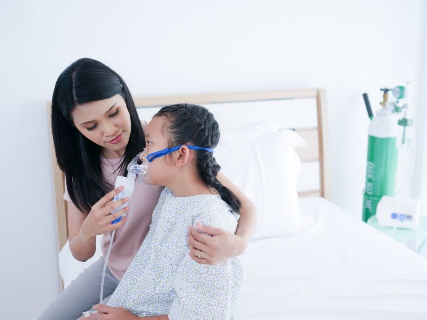 Dziewczyna z mukowiscydozą siedzi na łóżku z matką