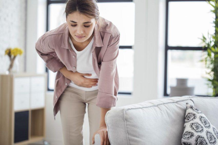 Kobieta zgina się z powodu ostrego bólu brzucha