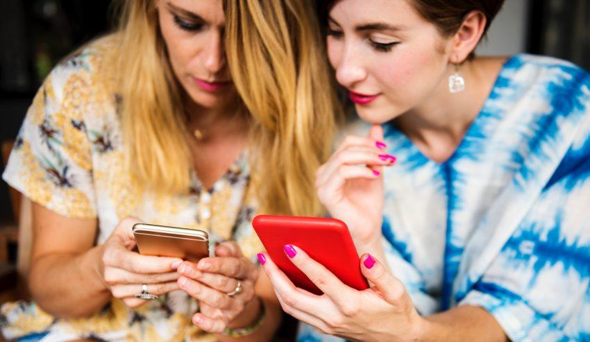 dwie kobiety korzystające ze smartfonów