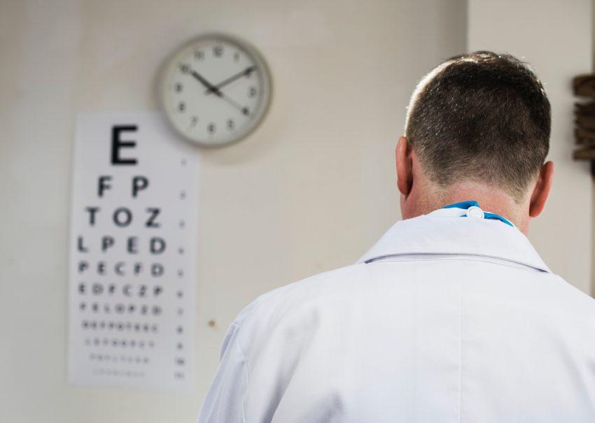 doktor stoi tyłem, na ścianieprzednimwisi zegar i tablica do sprawdzania wzroku