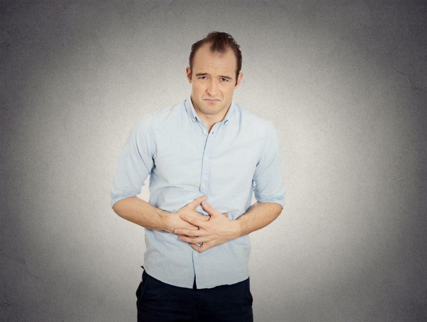 Mężczyzna trzyma się za brzuch, bo ma refluks żołądka