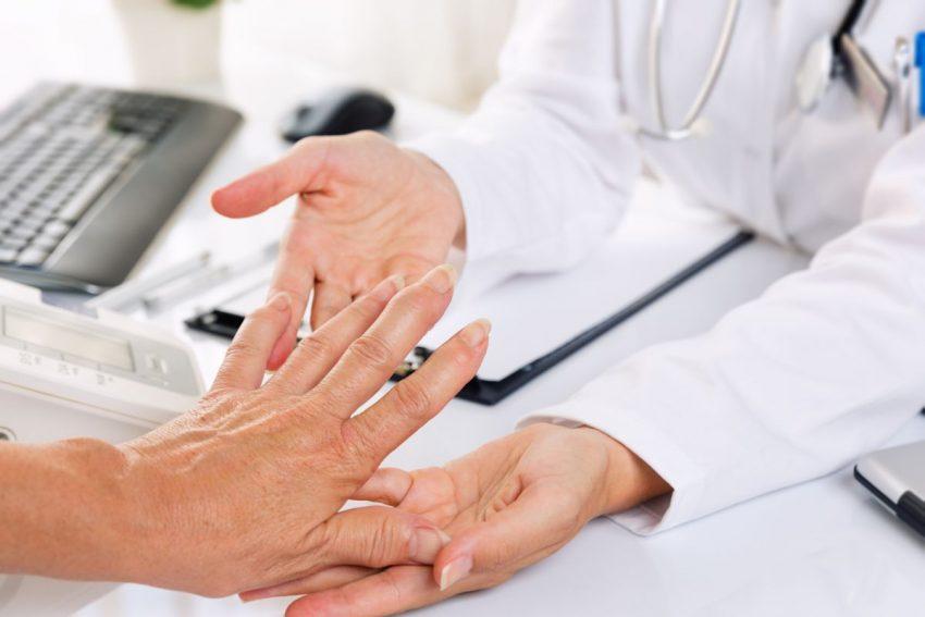 Lekarz dotyka dłoni pacjenta