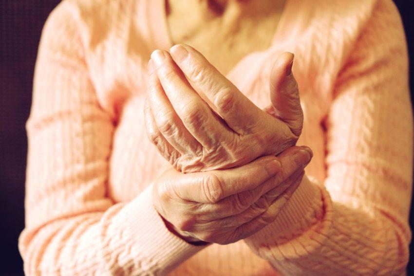 Starsza Pani trzyma się za rękę z powodu reumatoidalnego zapalenia stawów