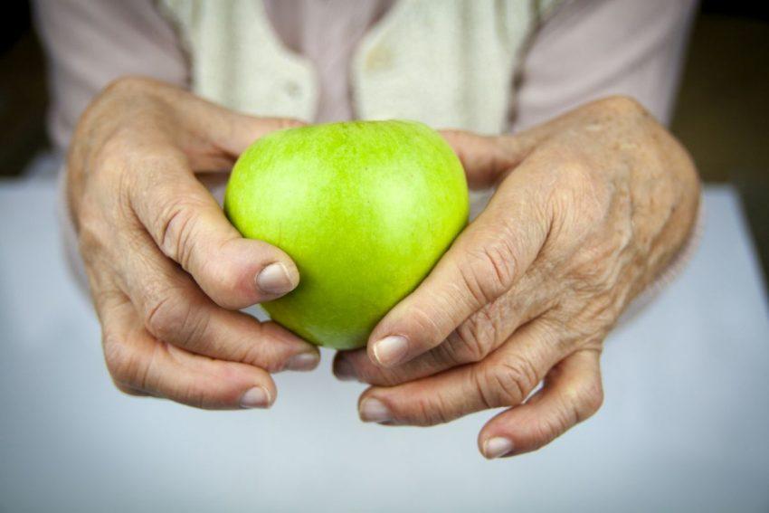 Starsza Pani trzyma w dłoniach jabłko