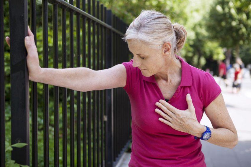 Kobieta z zawałem serca podtrzymuje się ogrodzenia