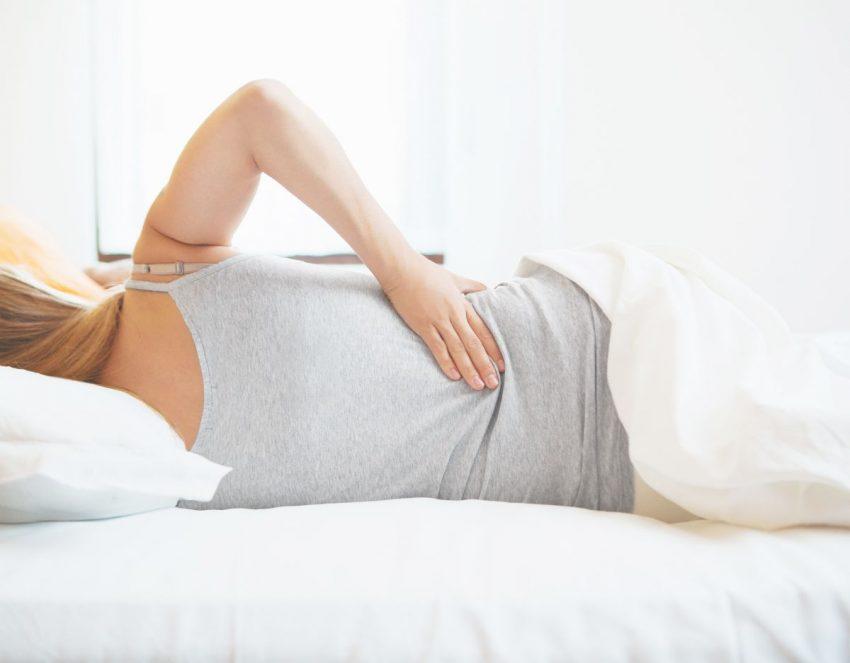 Kobieta leży w łóżku z powody objawów rwy kulszowej