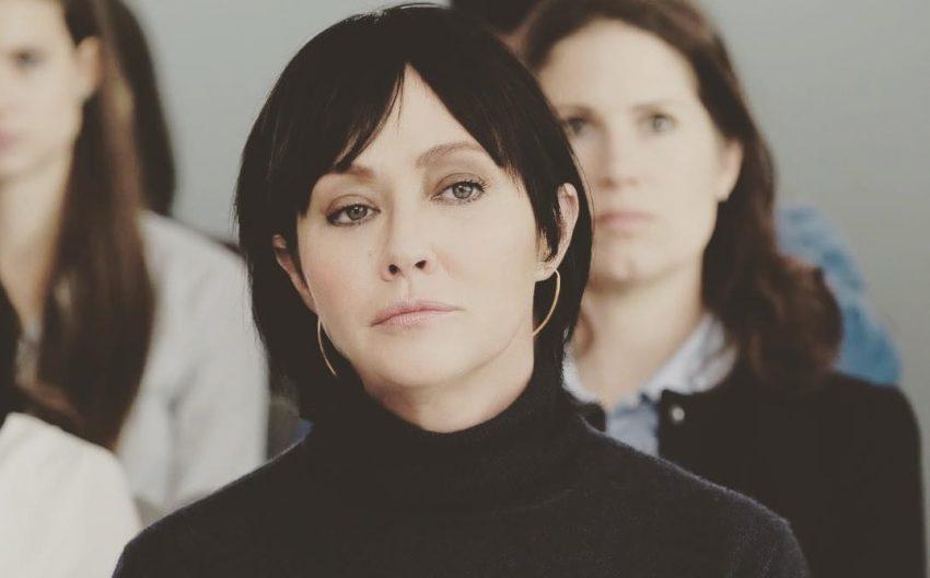 kobieta w czarnym swetrze siedzi na sali